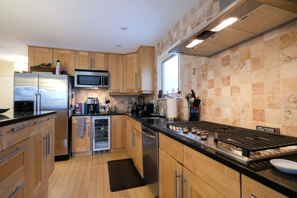 Stainless steel, hood, double GE oven, dishwasher and granite top island with plenty of storage.